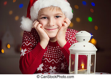Christmas child writing letter to Santa in red hat -...