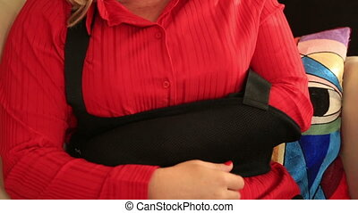 Portrait of a painful woman with a broken arm wearing arm...