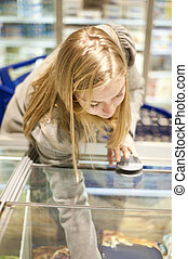 Frozen food - Young woman reaching in a freezer of the...