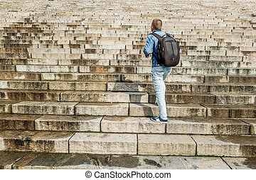 Male tourist climbs up the granite stairs - Male tourist...