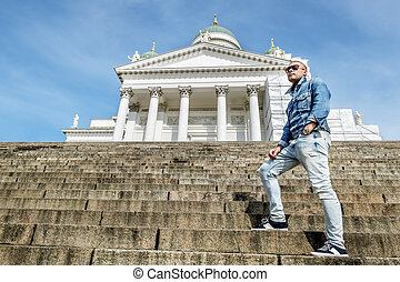 man stands on the granite stairs at the Cathedral on the Senate square in Helsinki.Finland.