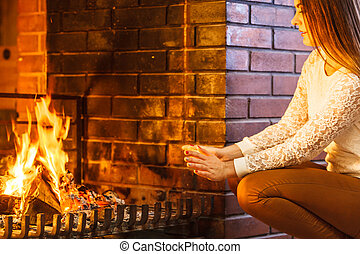 Woman warming hands up at fireplace. Winter home.