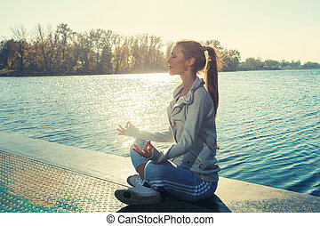 woman meditate on lake - young woman in tracksuit on pontoon...