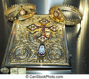 Cross, rings and crowns of gold on the table in church...