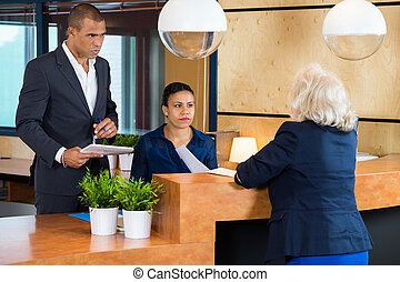 Businesspeople Talking To Receptionist In Office