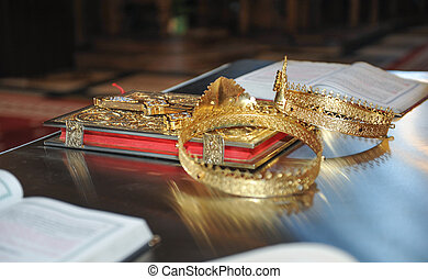 Cross, rings and crowns of gold on the table in church....