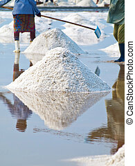Salt field - Farmer raking in the salt field in Thailand