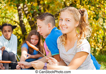Girl and teens sit on campsite with sausages near fireplace...