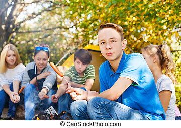 Boy and teens sit on campsite with sausages near fireplace...