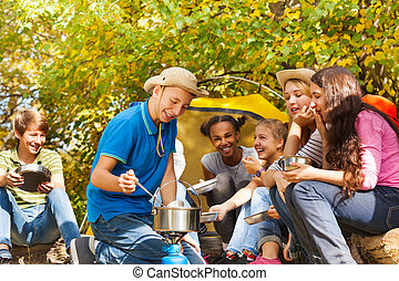 Boy cooks soup in pot for friends at campsite sitting near...
