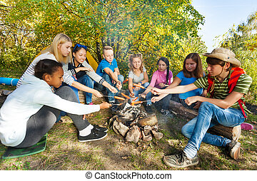 Teens grilling sausages on campsite sitting close - Teens...