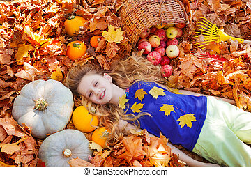 Portrait of beautiful girl on leaves with pumpkins and...