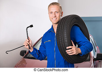 Smiling Mechanic Holding Tire And Wrench - Portrait Of A...