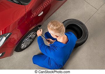 Mechanic Fixing Car Tire With Wrench - High Angle View Of...