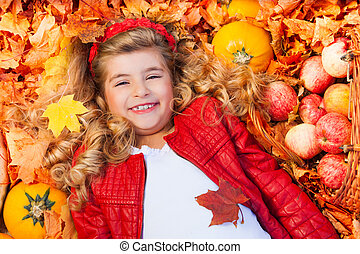 Girl laying on leaves with pumpkins, apples