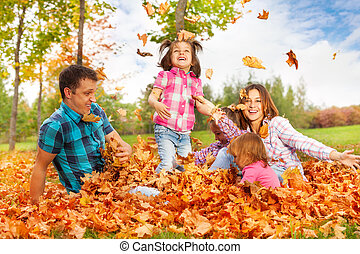 Mom and girls throw leaves up in the air