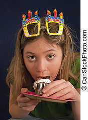 Birthday Taste - young adult eating birthday cupcake