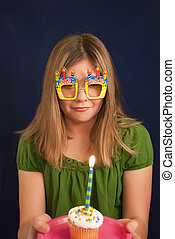 Birthday Fun - Young teen with birthday glasses, cupcake and...