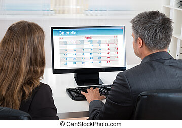 Two Businesspeople Looking At Calendar On Computer