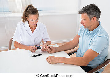 Doctor Checking Blood Sugar Level Of Patient - Female Doctor...