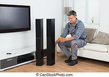 Technician Checking TV Speaker With Multimeter - Full length...