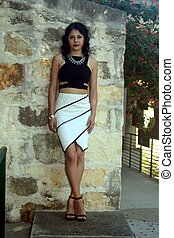 She Stands Out - model leaning against rock wall