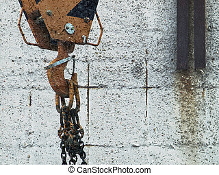 Hook crane in front of a concrete wall
