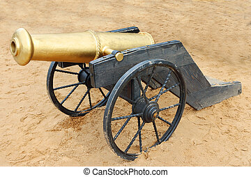 Old yellow metal cannon with black wheels on sand outdoor at...