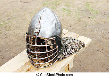 Closeup of metal medieval helmet with chain on wooden bench outdoor