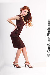 Full length beautiful young girl with red hair and brown dress
