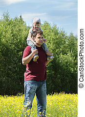 Man with little daughter on shoulders among yellow flowers at meadow at summer day