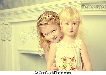 little sister - Two angelic sisters in white dresses hugging...