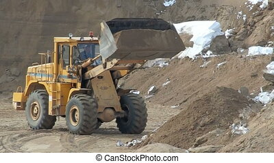 View of wheel loader unloads sand in sandpit - View of wheel...