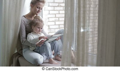 Blonde girl and mother using tablet