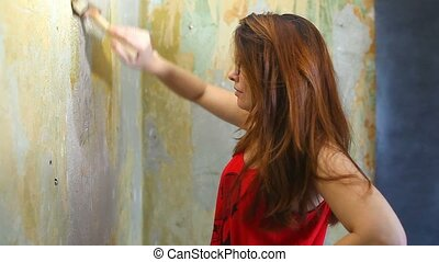 woman painter paints the wall repair work in the apartment -...