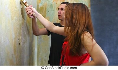 woman and man working family house painter paints the wall...