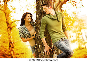 Hiding Behind A Tree - Young guy and girl in the park, play...