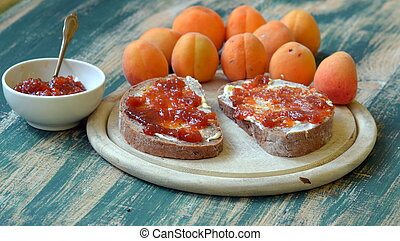 Apricot jam spread on bread with apricots on background