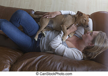 Woman and dog cuddling at home