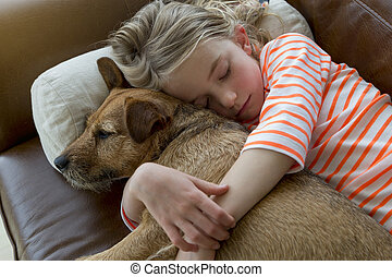 Young girl and her dog cuddling at home