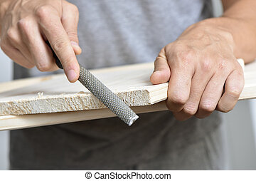 young man filing a wooden board with a rasp - closeup of a...