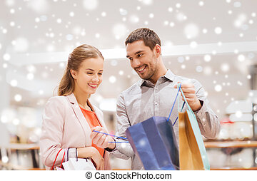 happy young couple with shopping bag in mall - sale,...