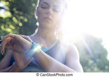 Keep an eye on that heart rate! - Young woman using a...