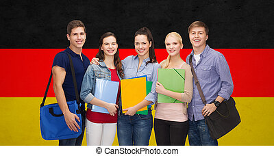 group of smiling students standing - education, learning and...