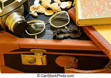 Vintage suitcase, camera, sunglasses, seashells, bracelet...