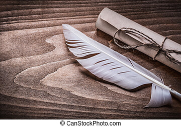Roll of vintage paper feather on wooden board