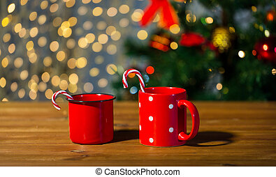 christmas candy canes and cups on wooden table - holidays,...