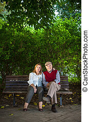 senior couple sitting on a bench in the park, Spain. They...