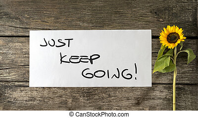Just keep going message written on white card lying next to a blooming yellow sunflower