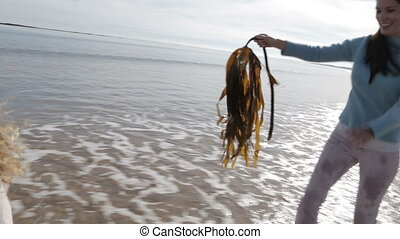 Mother Chasing her Daughter on the Beach with Seaweed - A...